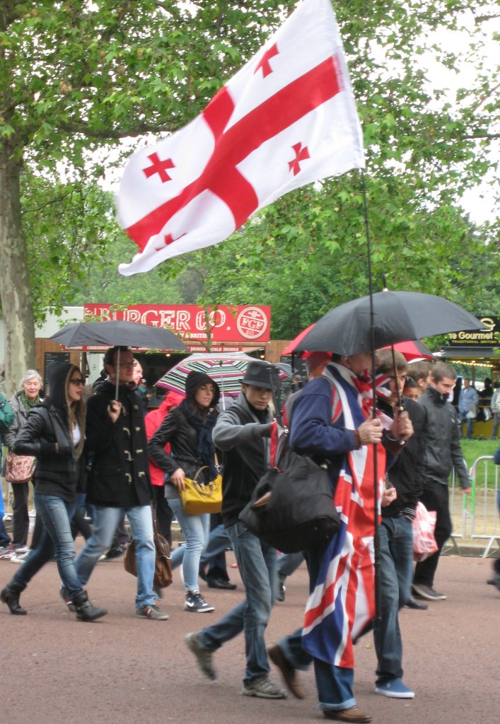 Jubilee weekend.  Brollies are up for a moment but the crowds don't care.  Notice the layers of clothing. Photo by me