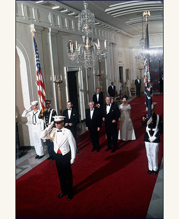 President and Mrs. Lyndon B. Johnson walk through White House Cross hall with guest of honor, Prime Minister Harold Wilson, June 1967